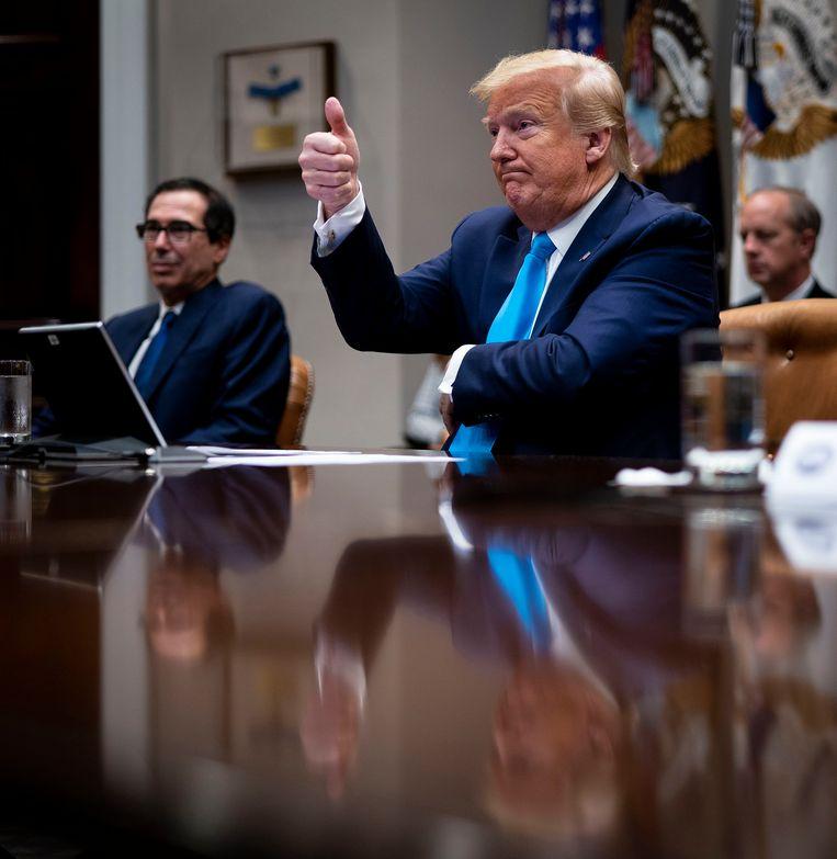 Toenmalig president Donald Trump en zijn minister van financiën Mnuchin tijdens een video-conferentie. Beeld Getty Images
