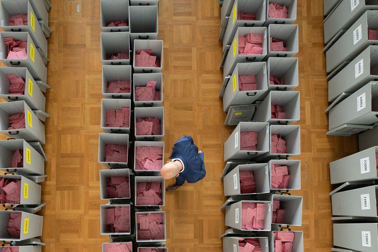 Dozen gevuld met verkiezingsenveloppen worden gecontroleerd in Dresden. Beeld Sebastian Kahnert/dpa-Zentralbil