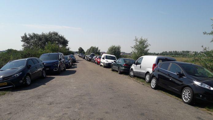 Auto's geparkeerd in de bermen van de Sint-Bavodijk in Nieuwvliet-Bad, dichtbij de strandovergang.