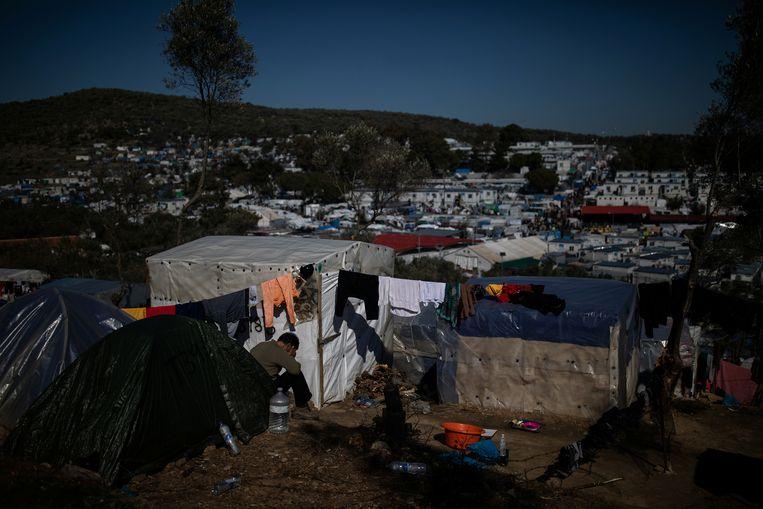 Een man bij zijn tent in een vluchtelingenkamp op Lesbos. Beeld REUTERS