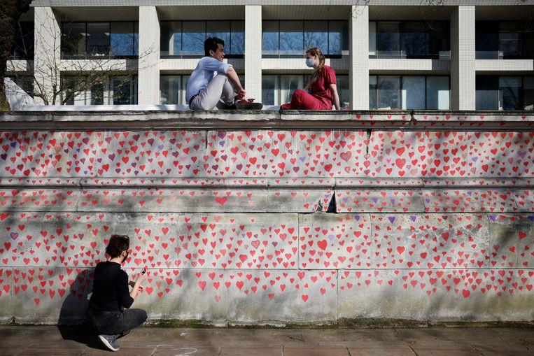 Op een muur bij het St Thomas Ziekenhuis in Londen zijn honderden hartjes getekend ter nagedachtenis aan de slachtoffers van het coronavirus. Beeld AFP