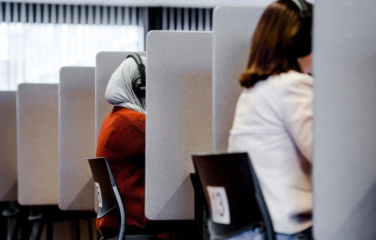 Een mevrouw maakt een inburgeringsexamen op een toetslocatie van de Dienst Uitvoering Onderwijs. Beeld ANP