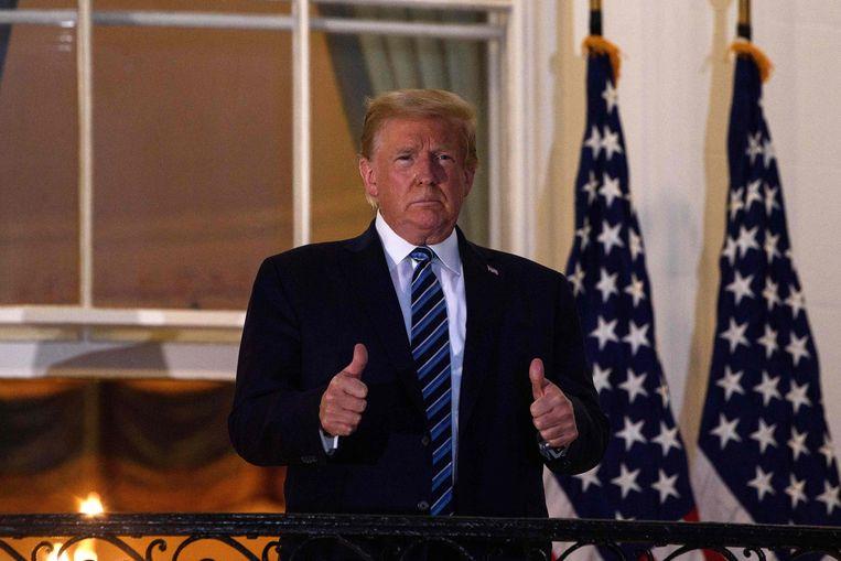 Donald Trump steekt zijn duimen op na zijn thuiskomst in het Witte Huis eerder deze week na zijn ziekenhuisopname. Beeld AFP