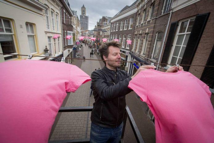 """Ontwerper Willem Jakobs zet de t-shirts met speciale klemmen vast op de waslijn boven de Koningstraat. """"Met gewone wasknijpers red je het niet."""""""