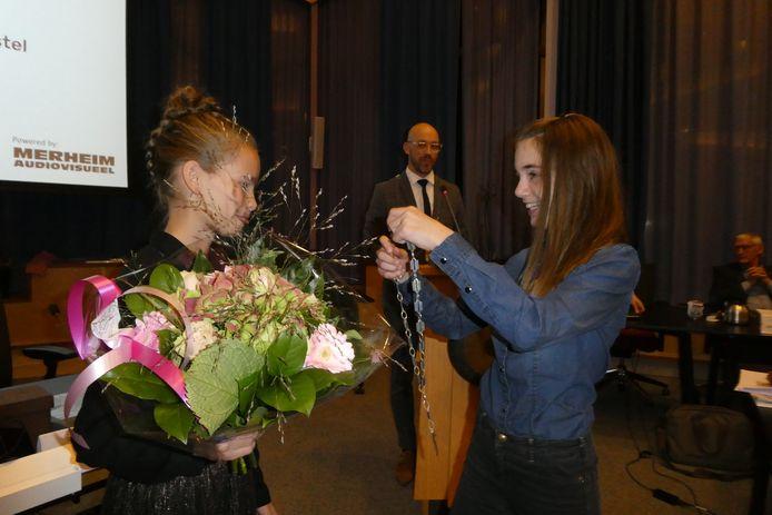 Michelle hangt de ambtsketen voor kinderburgemeesters om bij haar opvolger: Madelief Houtman.
