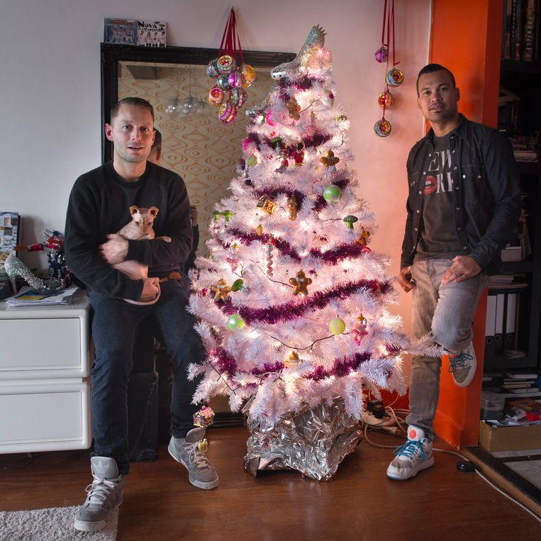 Erik Huygens (links), zijn vriend Donny Latupeirissa en kat Moos. Ze hebben weinig boodschap aan de volkswijsheid dat het ongeluk brengt als de kerstboom na Driekoningen, 6 januari, nog in huis staat. Beeld Joost van den Broek