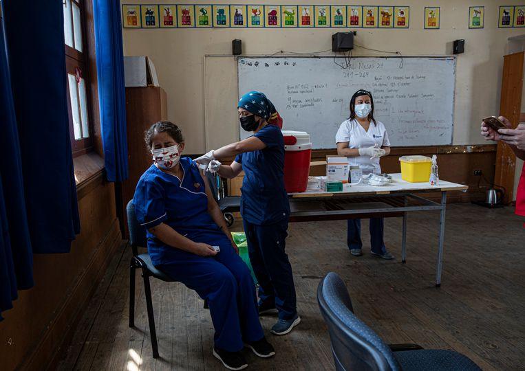Een leraar krijgt een injectie van het Chinese CoronaVac-vaccin van Sinovac Biotech op de openbare school van Salvador Sanfuentes. Beeld AP/Esteban Felix