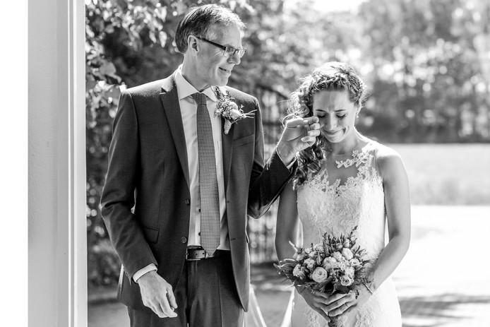 Vader Jos Masselink veegt een traan van het gezicht van zijn dochter Moniek, vlak voor hij haar naar haar toekomstige man begeleidt en haar 'weggeeft'.  Deze foto is genomineerd voor de prestigieuze Bruidsfoto Award 2020.