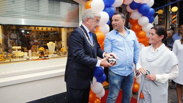 Juwelier Sylvia van den Berg (r), burgemeester Van Zanen en Sidney Bontrop van RDS lieten samen het rolluik neer