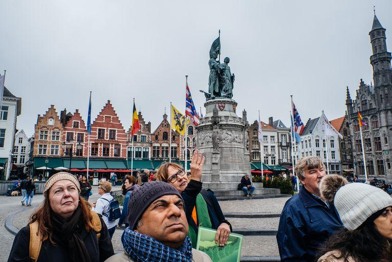 Toeristen op de Grote Markt in Brugge. Beeld Wouter Van Vooren