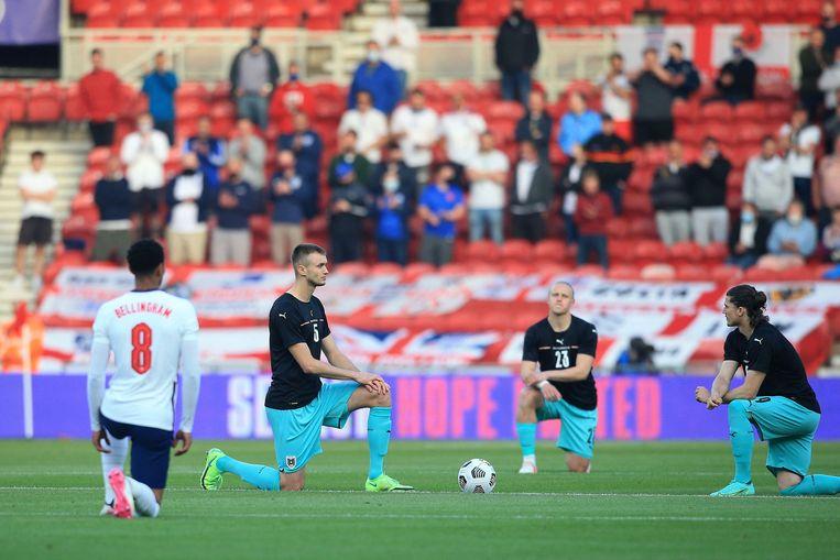 Spelers van Engeland en Oostenrijk knielen  voorafgaand aan het vriendschappelijke duel tussen beide landen van vorige week. Beeld AFP