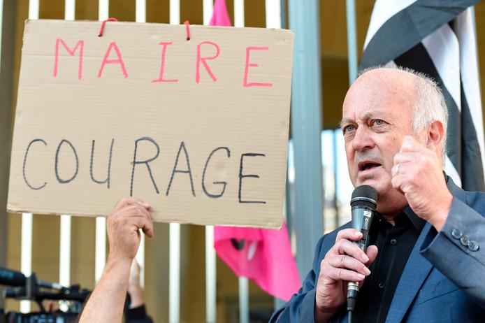 Burgemeester Daniel Cueff vorige week voor het gerechtsgebouw naast een bord van demonstranten die hem een 'dappere burgemeester' noemen vanwege zijn strijd tegen pesticiden.