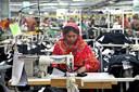 Een textielarbeider aan het werk in een fabriek in Bangladesh.