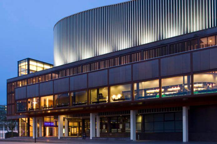 Achter de rood verlichte ramen van de concertzaal spelen vrijdagavond tien 'muziekwerkers'.