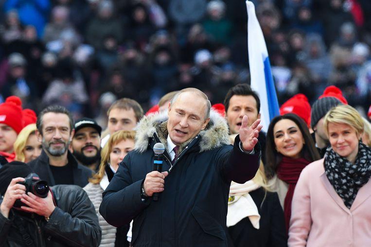 Poetin doet het al zijn hele regeerperiode: geld uitgeven aan gezinnen. Beeld AFP