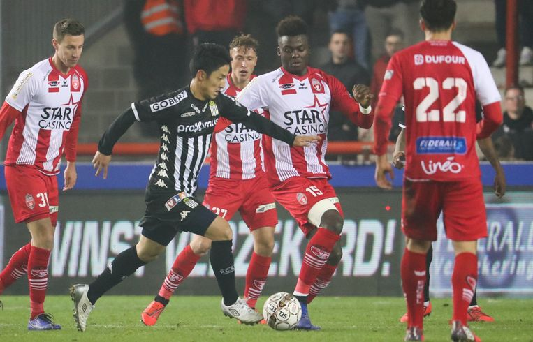 Moeskroen-spelers proberen Ryota Morioka (Charleroi) van de bal te zetten. Als shirtsponsor heeft Moeskroen het gokkantoor Star Casino. Beeld BELGA