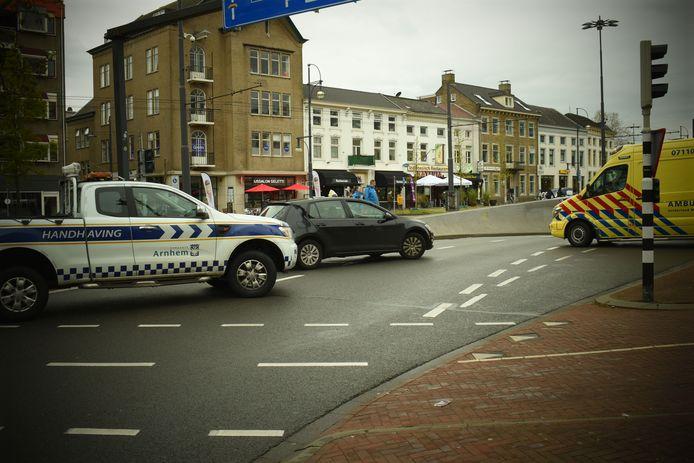 De ambulance rijdt de gewonde automobilist weg bij de Willemstunnel in Arnhem die aan het einde van de zaterdagmiddag  beneden over de kop sloeg.