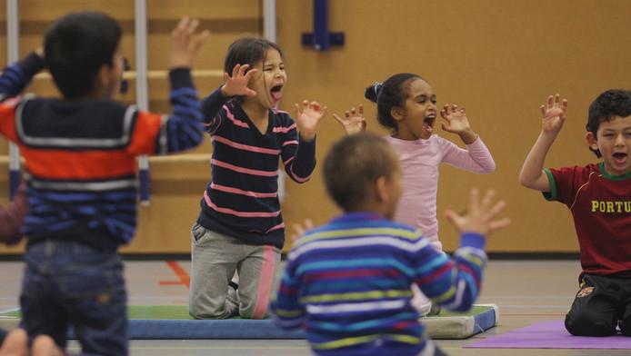 Groep 1/2 van Basisschool De Albatros in Dordrecht krijgt yogales in de gymzaal. 'Stel je voor dat je heel sterk bent en brul als een leeuw'.