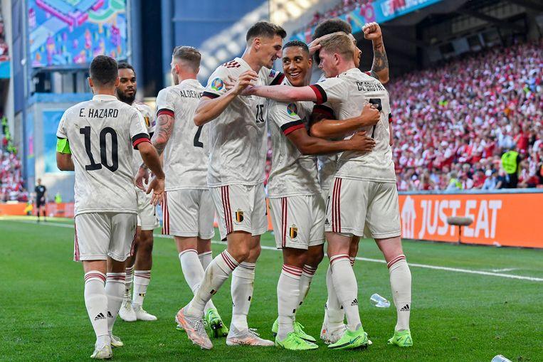 De Rode Duivels omhelzen Kevin De Bruyne na zijn bevrijdende doelpunt tegen Denemarken, donderdag in het Parken-stadion in Kopenhagen. Beeld Photo News
