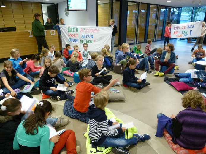 Leerlingen van groep 7&8 van basisschool De Schakel in Ammerzoden protesteren in de hal van het gemeentehuis tegen de voorgenomen bezuinigingen op de bibliotheken in Maasdriel.