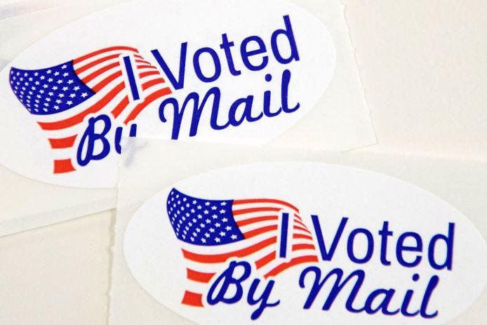 """Stickers met de tekst """"I Voted By Mail"""" liggen klaar om bij de briefstembiljetten te worden gestoken."""