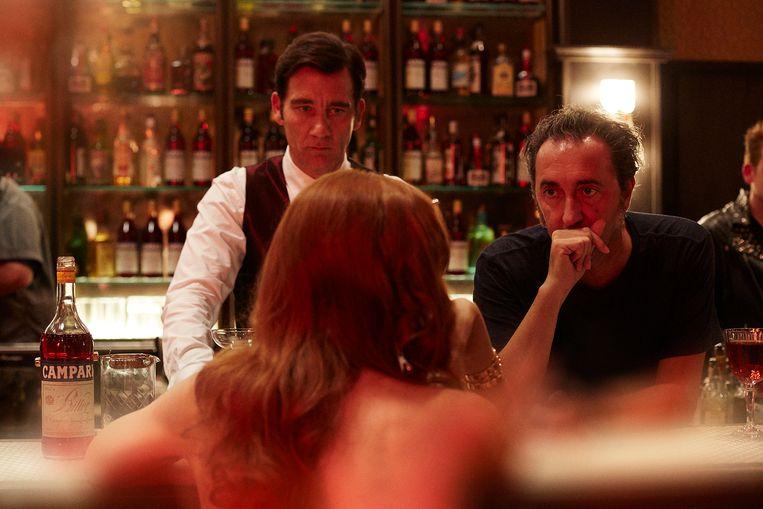 In 'Killer in Red' wordt een barman (Clive Owen) betoverd door een gevaarlijke vrouw.Rechts: regisseur Paolo Sorrentino. Beeld rv