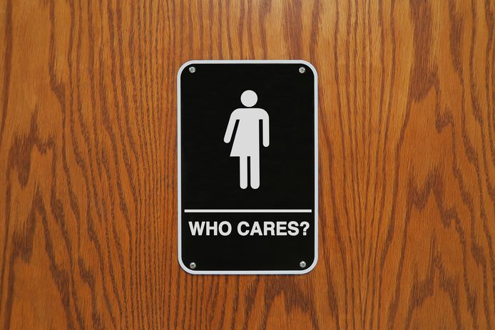 """Gender neutral restroom sign on a wooden door that says, """"Who cares?"""""""