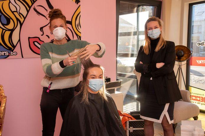 Kapster Annemie neemt de haren van Hanna onder handen. Kathy (Jobfixers) kijkt tevreden toe.
