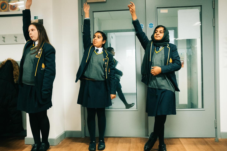 Leerlingen van de Michaela Community School steken hun hand omhoog. Zo goed als alle leerlingen hebben een migratieachtergrond.  Beeld Illias Teirlinck