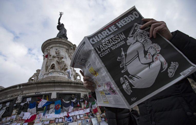 Charlie Hebdo wordt gelezen op de Place de la Republique. Beeld epa
