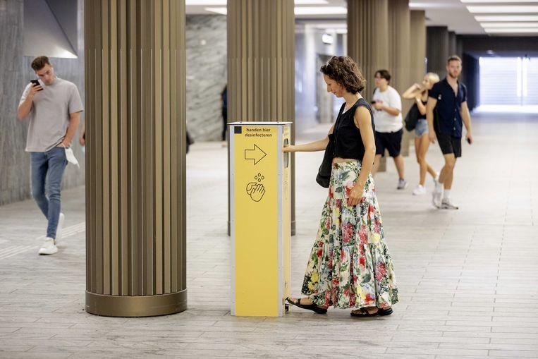Een reiziger maakt gebruik van een desinfectiezuil op het station van Breda.  Beeld ANP