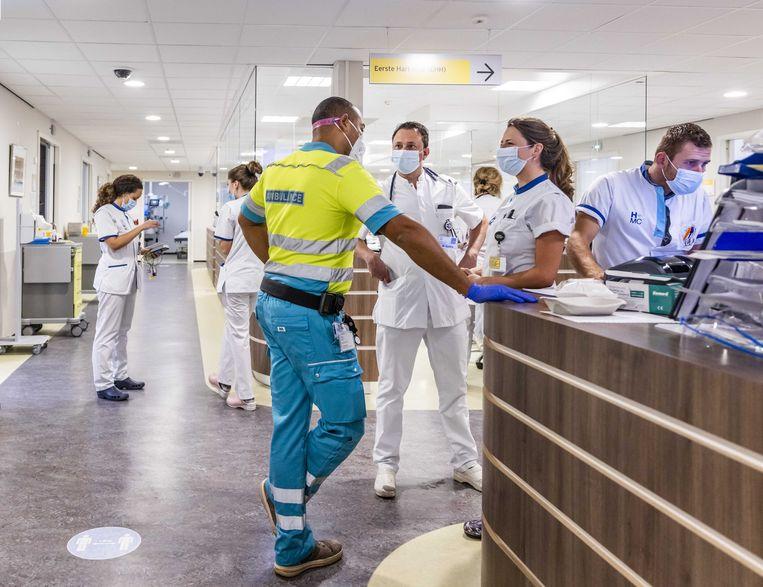Een ambulancebroeder overlegt met artsen in het HMC Westeinde in Den Haag. Beeld ANP