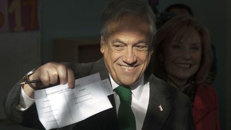 De Chileense president Sebastián Piñera toont zijn stembriefje bij verkiezingen in Santiago, eind juni. Beeld afp