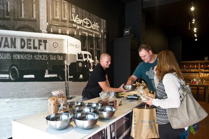 Bezoekers proeven de pepernoten in de winkel Van Delft.