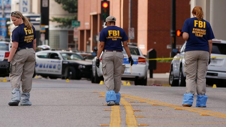 Medewerkers van de FBI onderzoeken de plek in Dallas waar vijf agenten werden gedood en zeven anderen gewond zijn geraakt. Beeld reuters