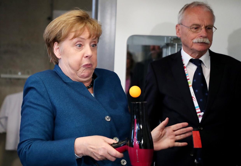 Bondskanselier Angela Merkel in de weer met een föhn en een balletje tijdens een bezoek aan de jeugduniversiteit in Wuppertal.  Beeld EPA