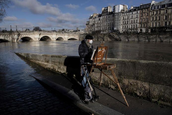 Een kunstschilder heeft zijn ezel naast de overstroomde Seine gezet om de Parijse rivier in volle glorie op het doek vast te leggen. Foto Christophe Archambault