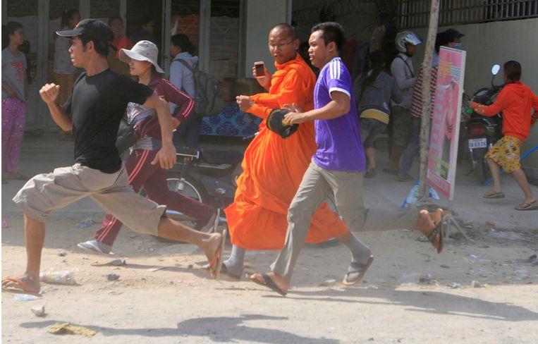 Arbeiders en een monnik vluchten voor troepen die een manifestatie van textielarbeiders uiteenslaan in Cambodja. Beeld AP