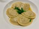 Ravioli met vulling van coquille, tonijn en zeewier, met daslookboter en een plukje zeewiersalade.
