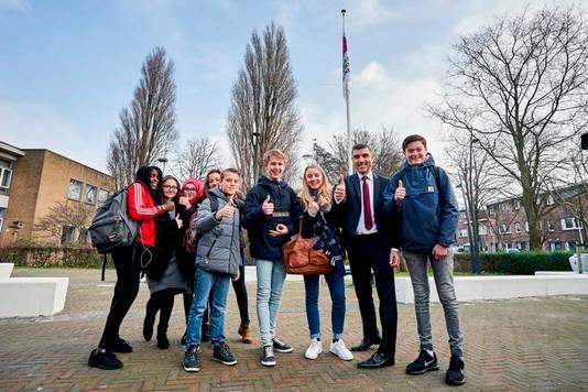 Samen met leerlingen van het Segbroekcollege hijst Blokhuis de vlag op het schoolplein.