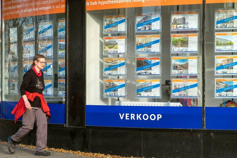 De in de verkoop staande woningen in de vitrine van een makelaar in Schiedam zijn bijna allemaal al verkocht. Beeld Hollandse Hoogte / Hans van Rhoon