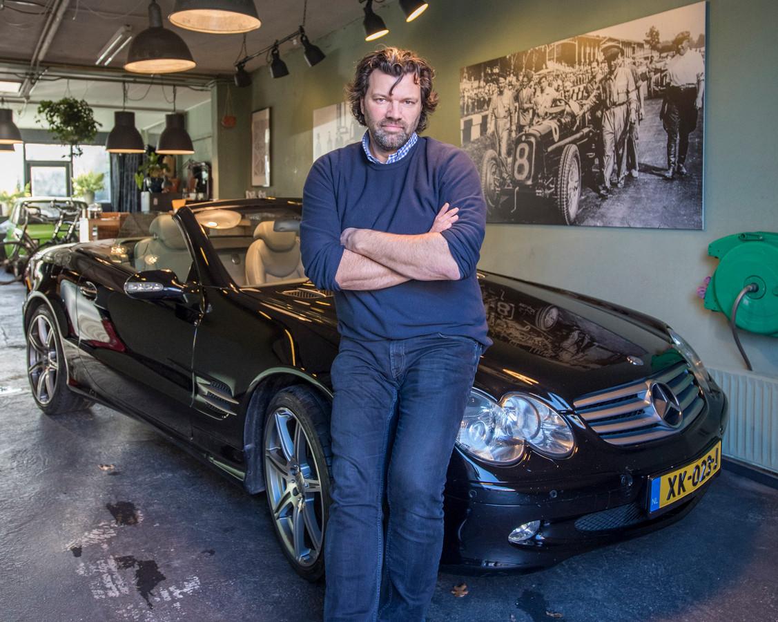 Michel van Rheenen in zijn garage met een Mercedes 500SL cabrio.