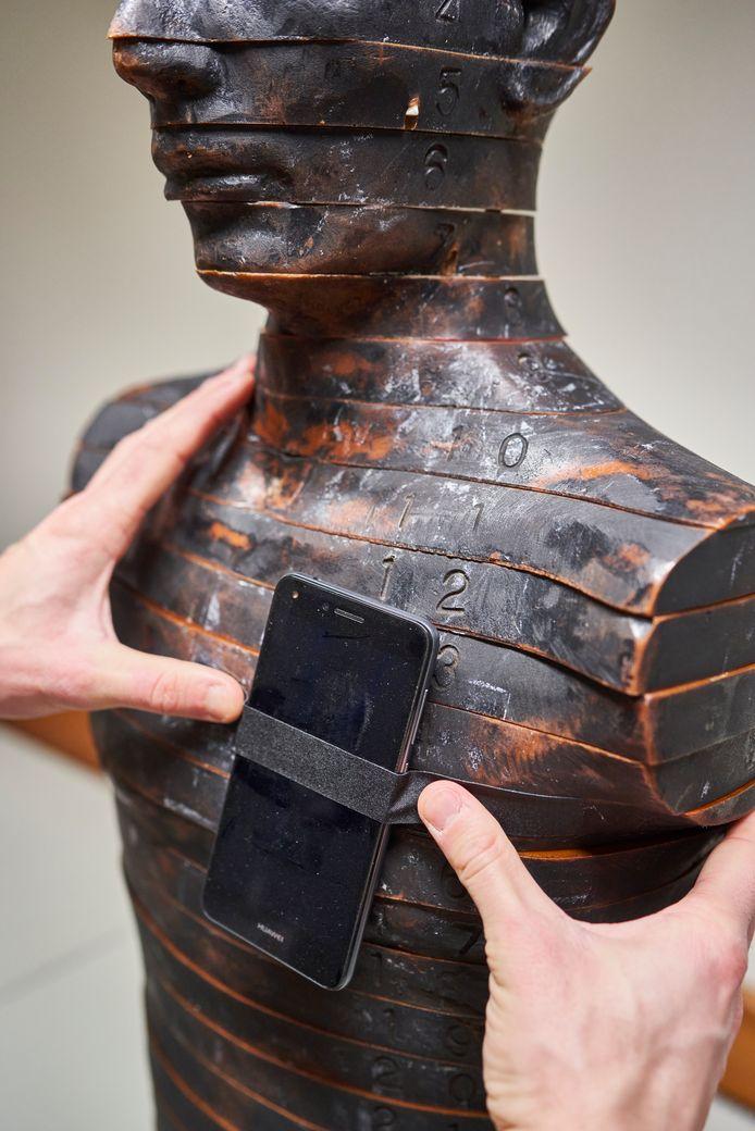 Onderzoeker SCK CEN bevestigt smartphone op een anatomische torso.