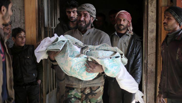 De vader van een meisje van 10 draagt haar lichaam naar buiten voor de begrafenis. Het kind is omgekomen bij luchtaanvallen in Ghouta. Beeld afp