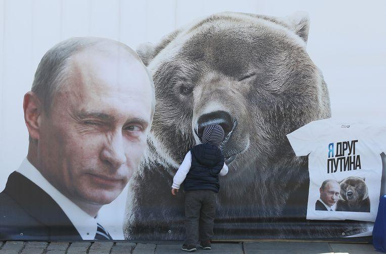 Een jongetje loopt voorbij een affiche van Russisch president Poetin. Op een T-shirt prijkt het opschrift: 'Ik ben een vriend van Poetin'. Beeld GETTY