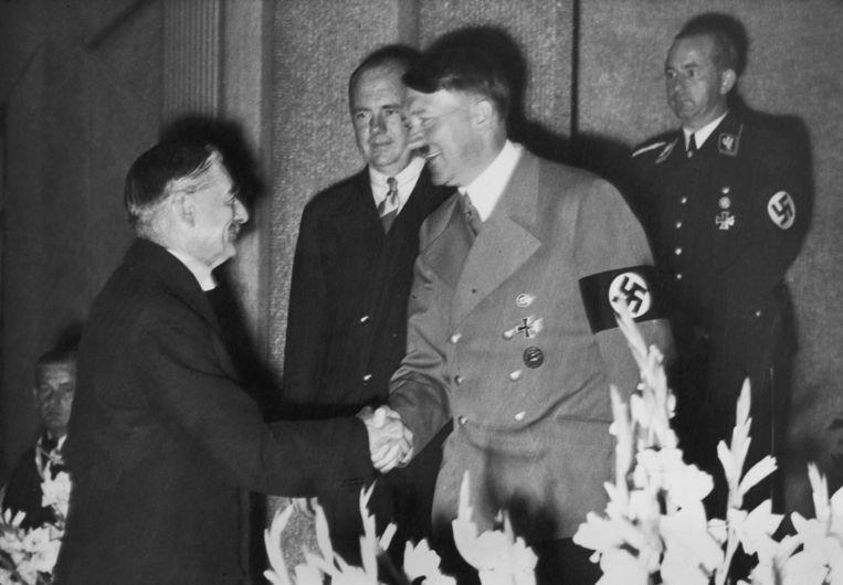 De Britse premier Neville Chamberlain schudt handen met de Duitse nazidictator Adolf Hitler op 22 september 1938. Beeld Getty Images