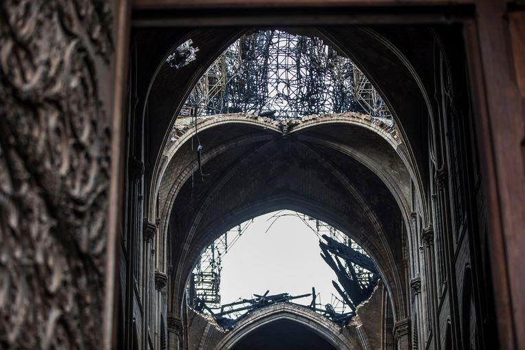 De koepel van de Notre-Dame is zwaar beschadigd door de brand van maandag. Beeld AP
