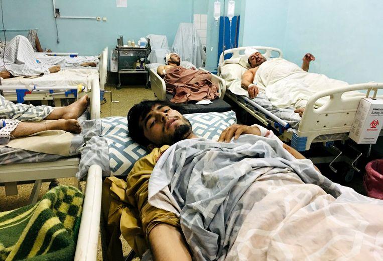 Gewonde Afghanen donderdagavond in Kabul, na de dubbele aanslag bij het vliegveld.  Beeld AP