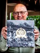 Martin Bauman toont het jubileumboek van ALTA, dat honderd jaar bestaat,