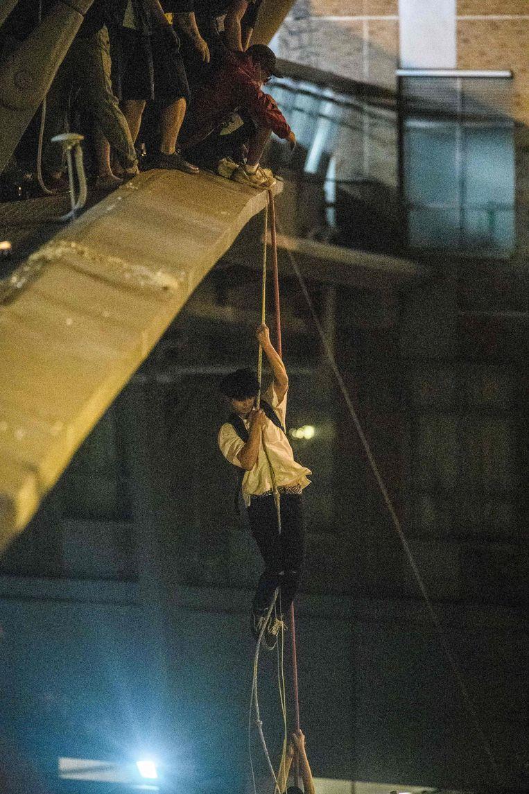 Een student klautert met een touw naar beneden. Beeld AFP